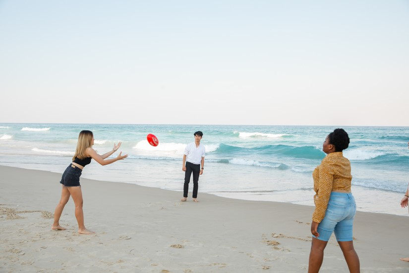 Group of Griffith College students throwing a football around at the beach