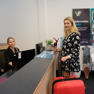 Female Griffith College student checking in to campus accommodation reception with suitcase