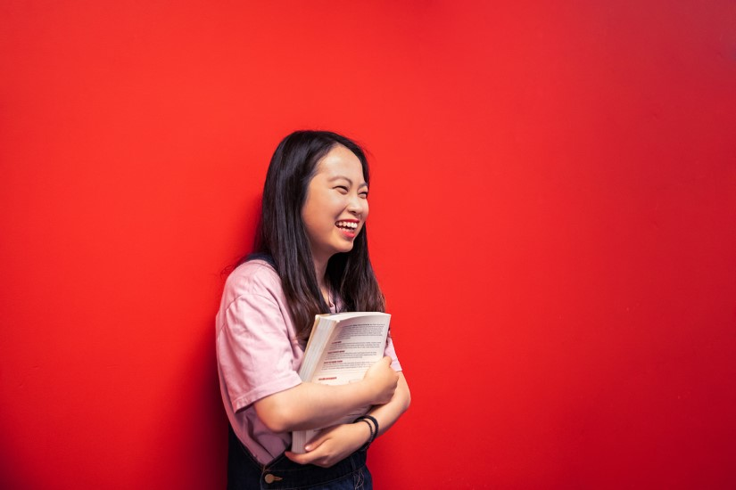 Female Korean Griffith College student smiling against red wall while hugging a textbook