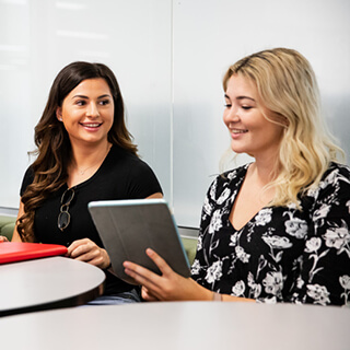 Two female Griffith College students discussing over ipad