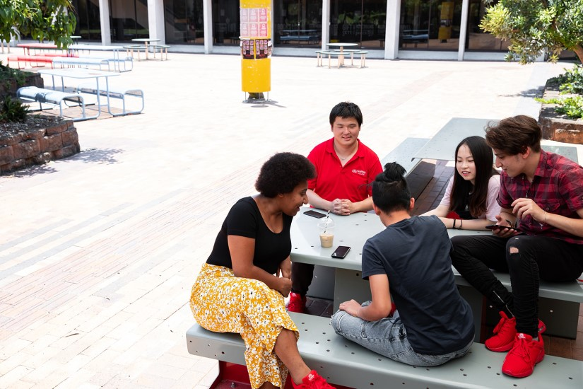 Group of Griffith College students sitting together in the courtyard talking
