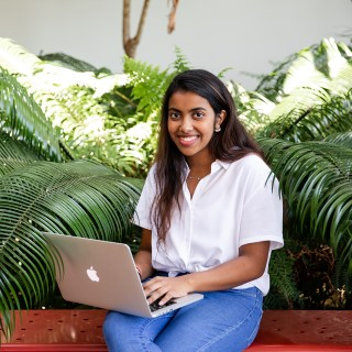 Female Griffith College student sitting down with MacBook smiling at camera