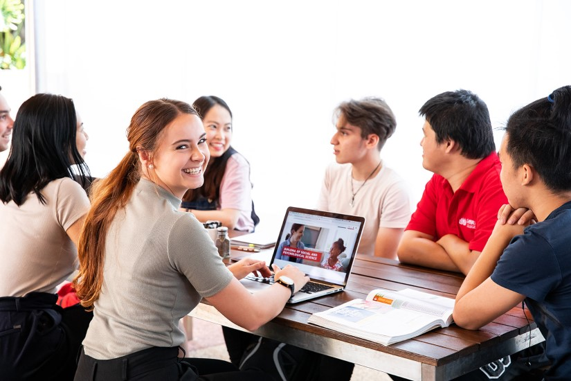 female Griffith College student smiling at camera while using laptop with a group of friends