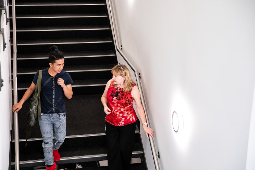 Male Griffith College student walks down stairs while chatting with student learning advisor