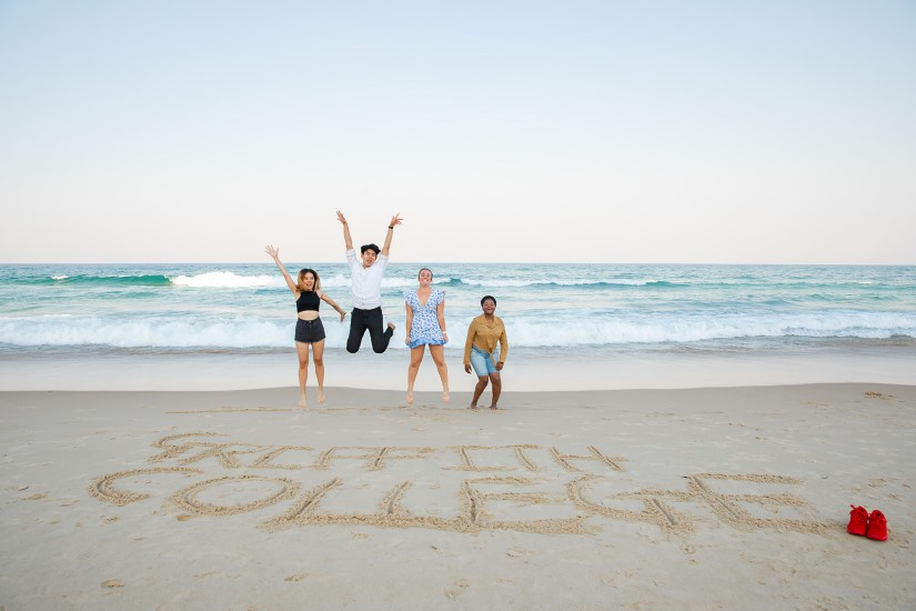 Group of Griffith College students performing a jumpshot by the beach in front of writing