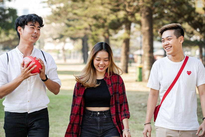 Three Griffith College students walking together with red football