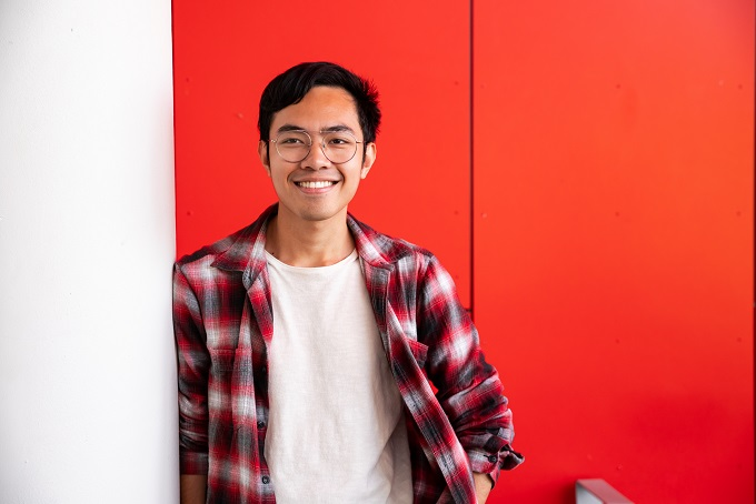 Philippines male student leaning on a post smiling at the camera with red backdrop