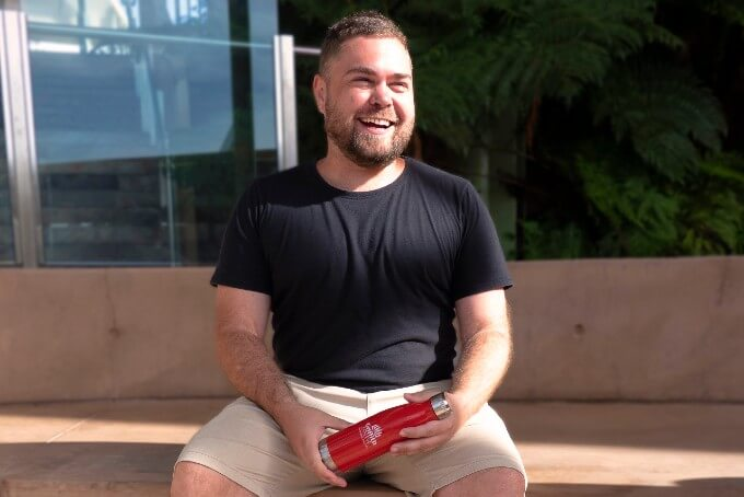 Australian male Griffith College student sitting down holding red water bottle